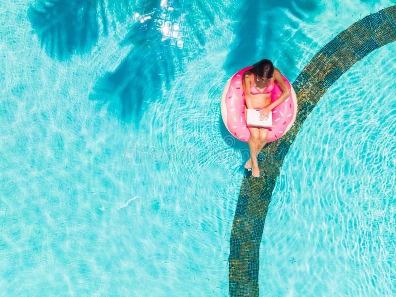 坐与在一个可膨胀的圈子的一种片剂的年轻女性自由职业者在水池 r 免版税图库摄影