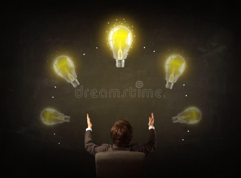 坐与在他的头的电灯泡的商人 库存图片