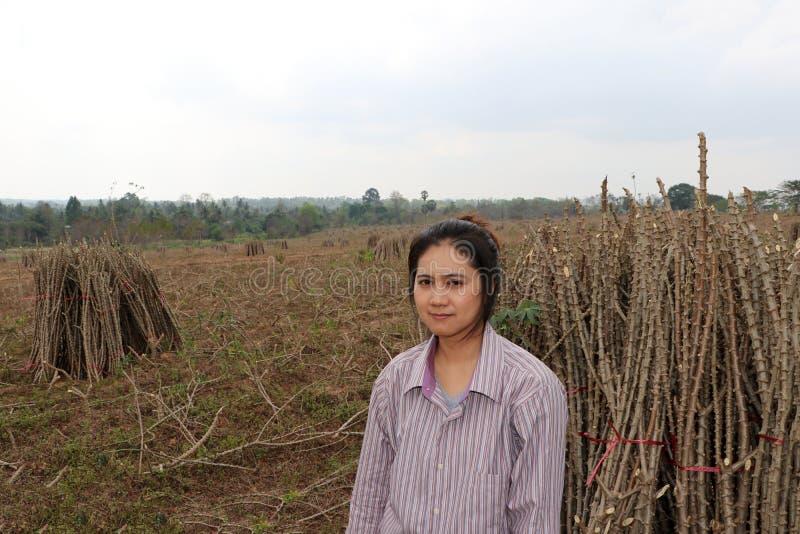 坐与在农场一起切开堆的珍珠粉肢体的女性农夫 免版税库存图片