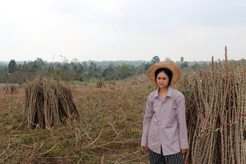 坐与在农场一起切开堆的珍珠粉肢体的女性农夫 免版税库存照片