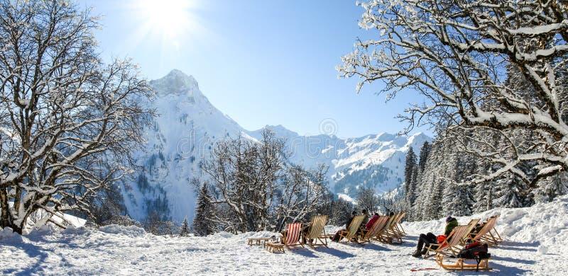 坐与在冬天山的轻便折叠躺椅的人 晒日光浴在雪 德国,巴伐利亚, Allgau 免版税库存照片