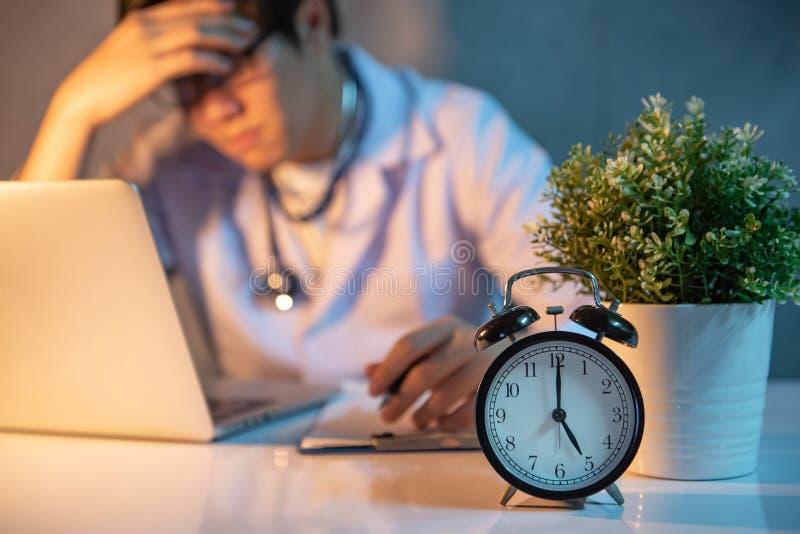 坐与在医院诊所的膝上型计算机的劳累过度的医生 库存照片