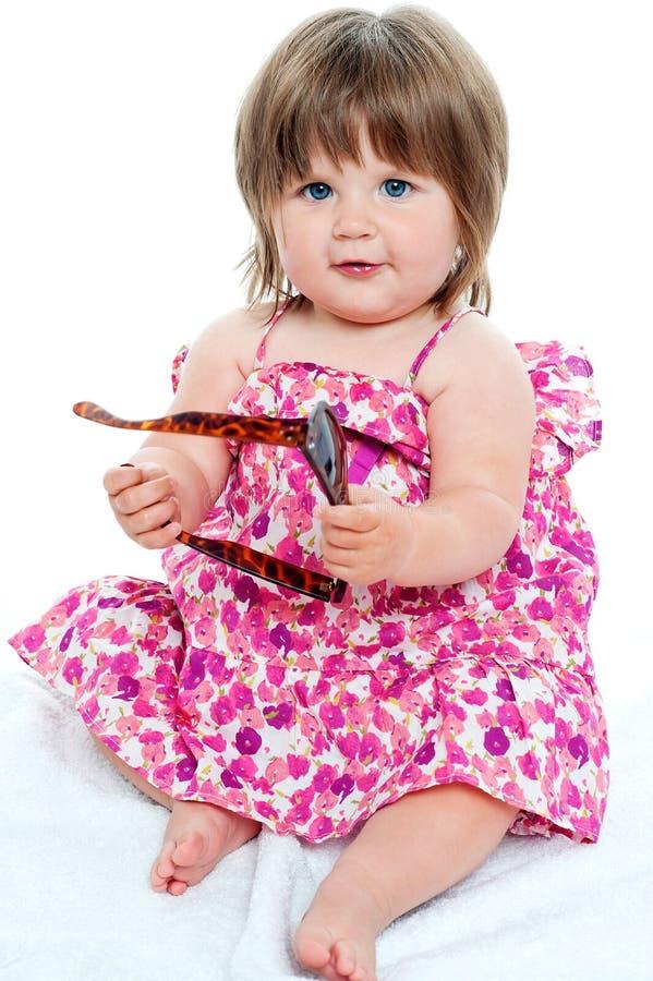 坐与在她的现有量的树荫的女婴 免版税库存照片