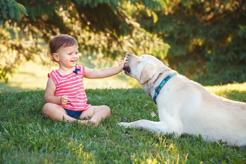坐与外面狗的女婴在公园 免版税库存图片