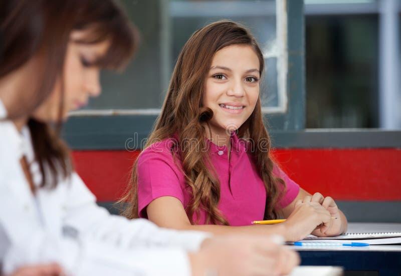 坐与女性朋友的少年女小学生 免版税库存照片
