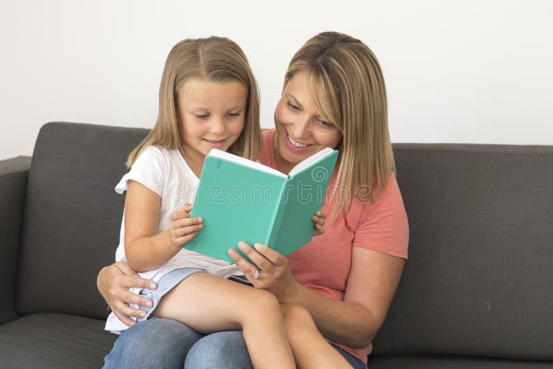 坐与她可爱的7岁一起的年轻美丽和愉快的妇女享用可爱的白肤金发的女孩的阅读书告诉s 免版税库存照片