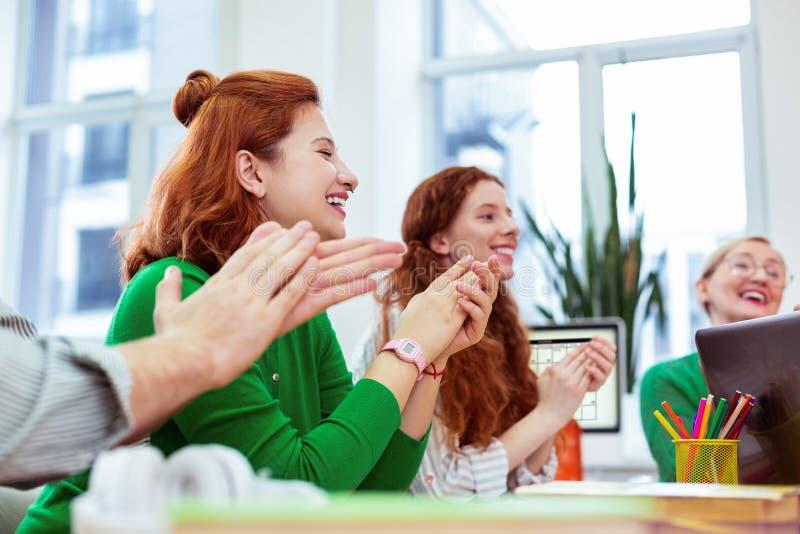 坐与她的同事的快乐的正面妇女 免版税库存图片