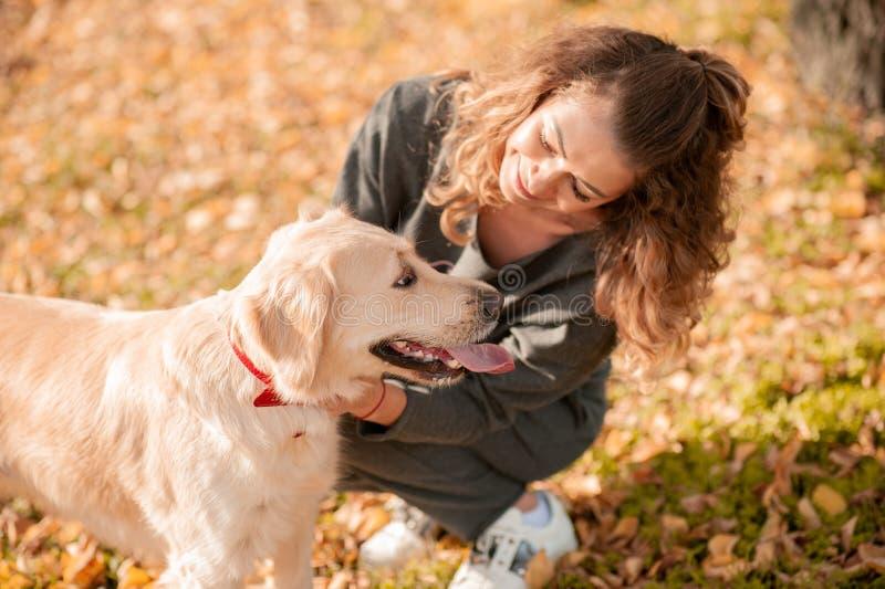 坐与她的在秋叶的狗的卷曲妇女特写镜头户外 免版税库存照片