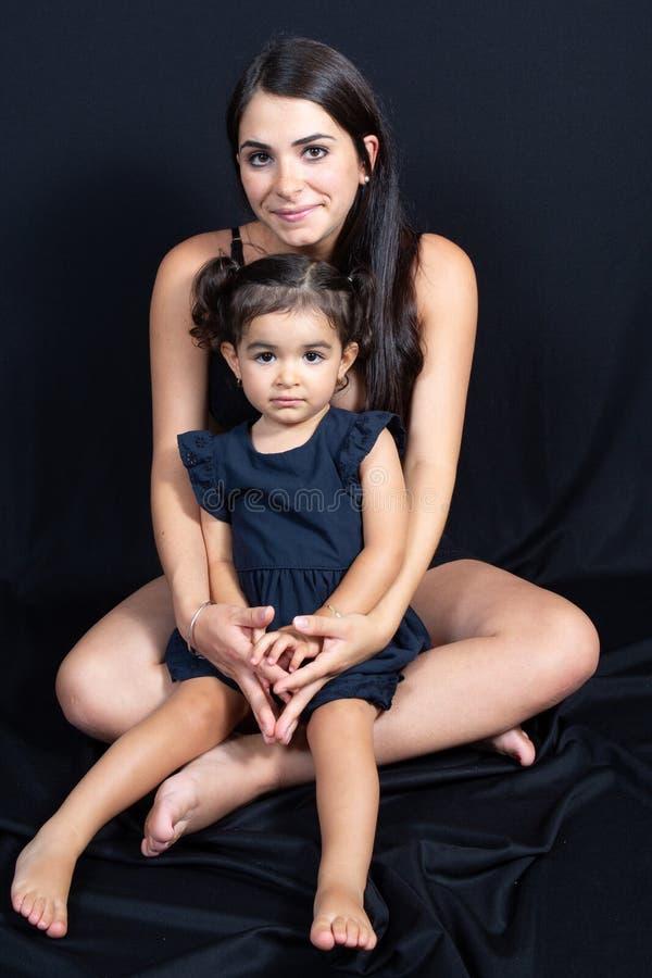 坐与她的女儿的母亲在黑地板墙壁演播室背景下 免版税库存照片