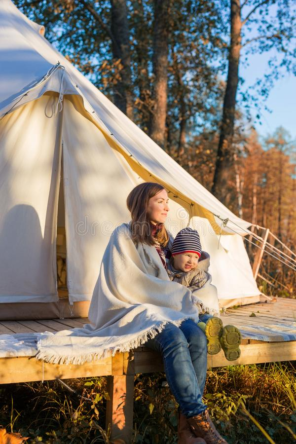 坐与她的孩子的年轻母亲在传统帆布钟形帐幕附近 库存图片