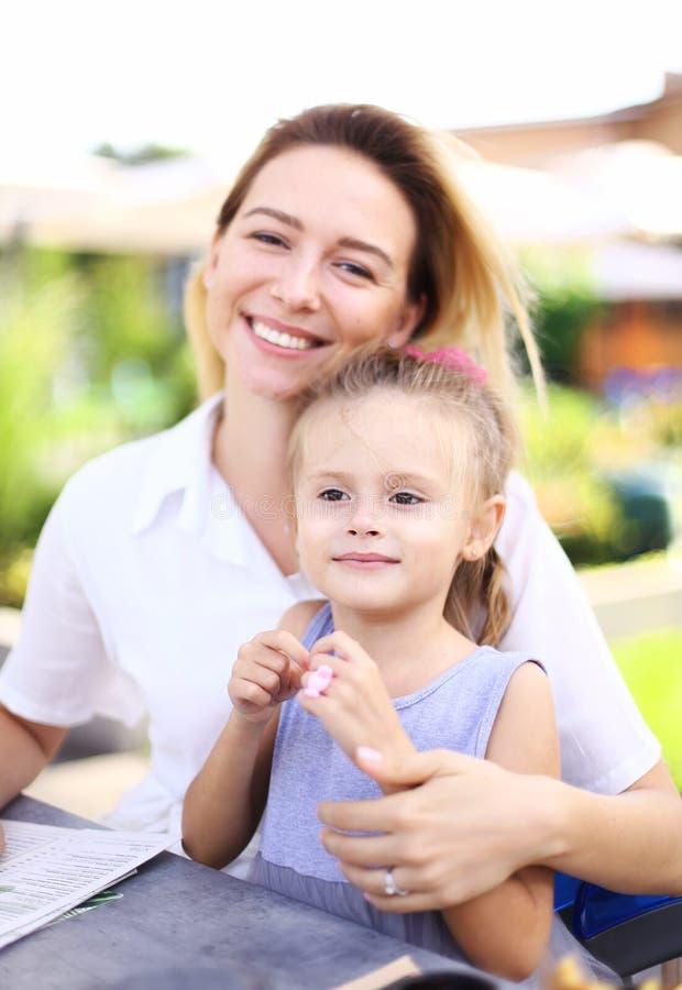 坐与小女性孩子外部和微笑的愉快的年轻母亲 免版税库存照片