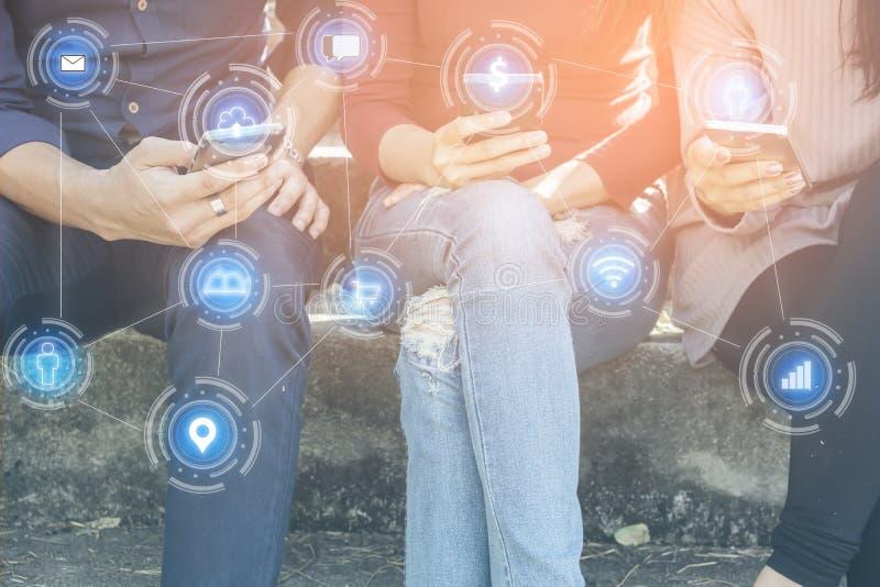 坐与巧妙的电话的亚裔青少年的朋友在手中连接到社会媒介用技术网络 免版税图库摄影