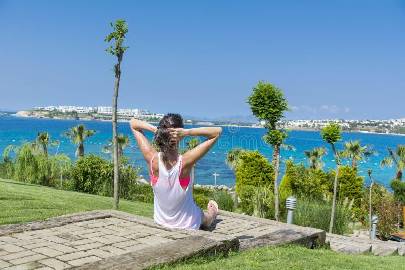 坐与开放胳膊的少妇画象在一个热带海庭院里 库存图片