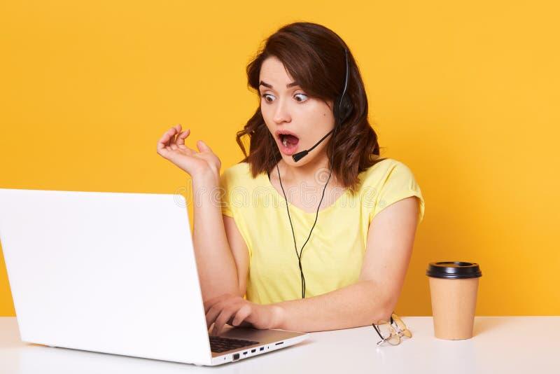 坐与张的嘴的妇女操作员半lengh照片,看laptopon屏幕,被隔绝在黄色背景  免版税库存图片