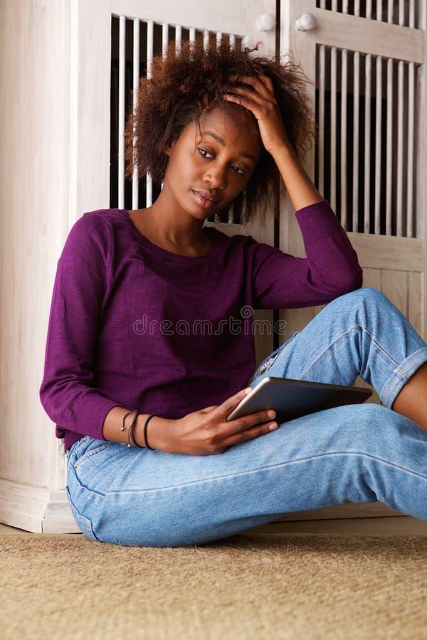 坐与数字式片剂的黑人妇女 免版税图库摄影