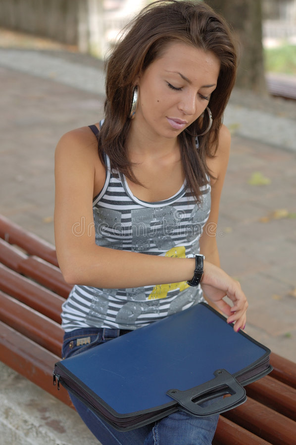 坐与文件夹的长凳的妇女 免版税库存照片