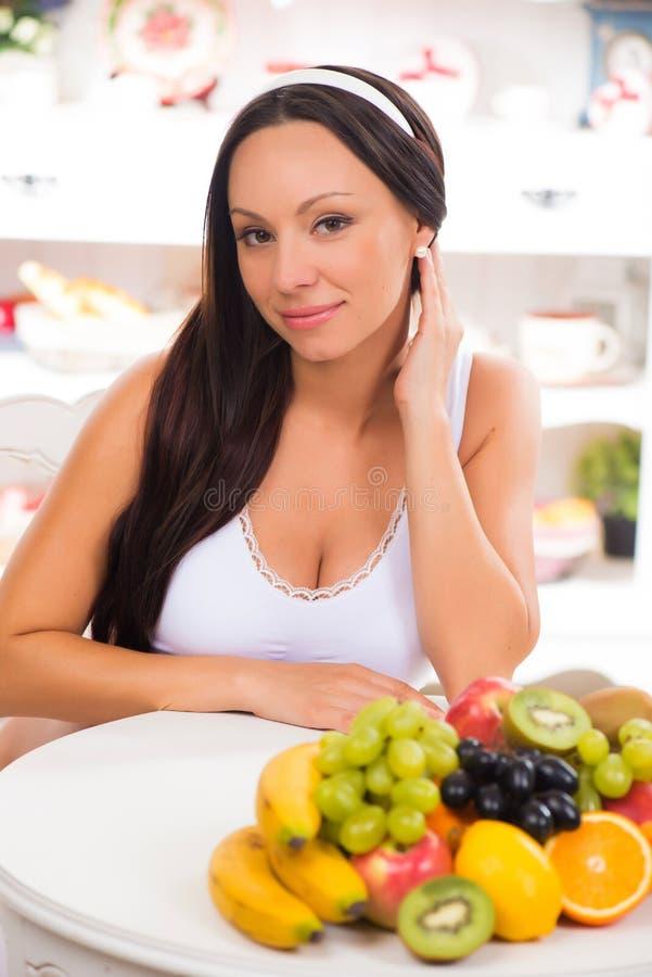 坐与新鲜水果板材的美丽的深色的女孩  饮食、健康食物和维生素 免版税库存照片