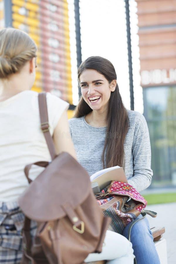 坐与朋友的微笑的十几岁的女孩在长凳在大学 免版税库存照片