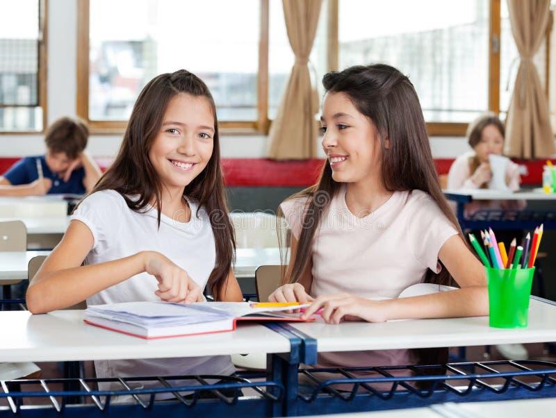 坐与朋友的愉快的女小学生在书桌 免版税库存图片