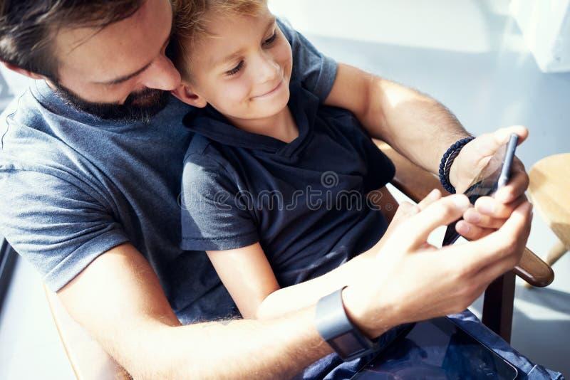 坐与父亲和使用手机的年轻男孩特写镜头在现代晴朗的地方 水平,被弄脏的背景 免版税库存照片