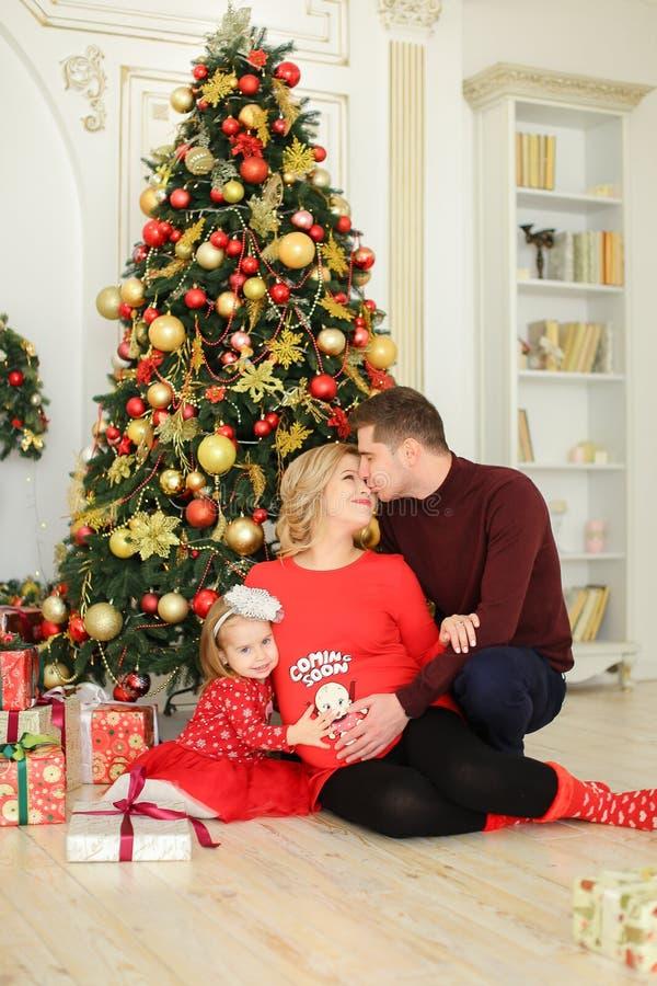 坐与父亲和怀孕的母亲在圣诞树附近和保留礼物的小欧洲女儿 免版税库存照片
