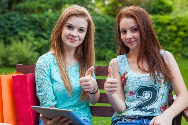 坐与片剂和赞许的两个相当女孩 库存照片