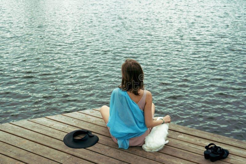 坐与狗的妇女在船坞在湖 库存图片