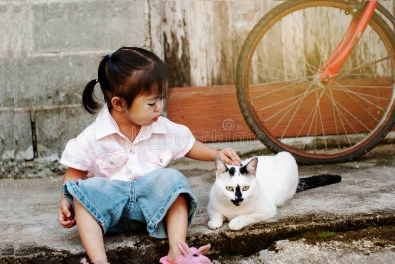 坐与猫的逗人喜爱的小女孩 免版税库存图片