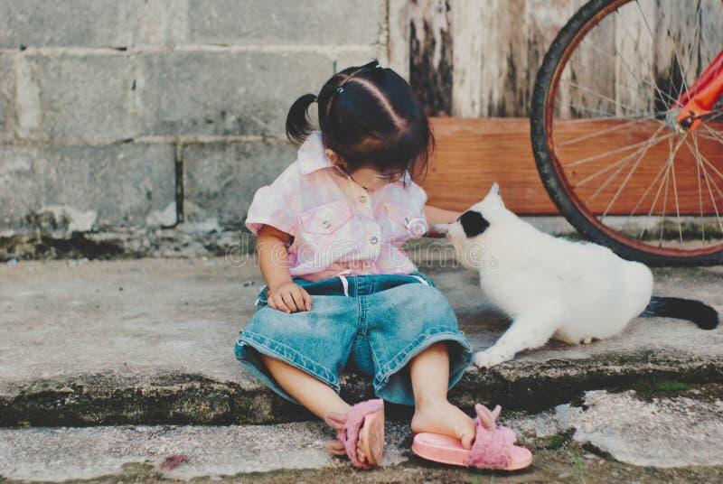 坐与猫的逗人喜爱的小女孩 免版税库存照片