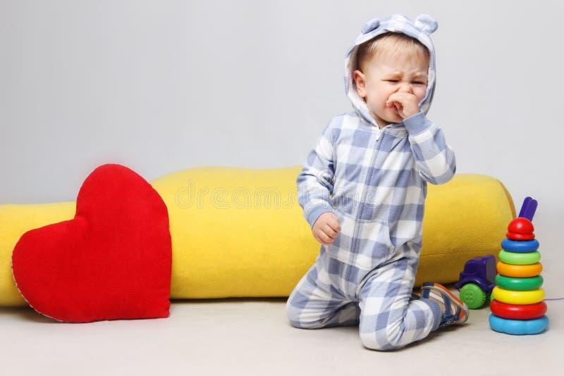 坐与玩具和哭泣的不快乐的矮小的男婴画象  免版税库存图片