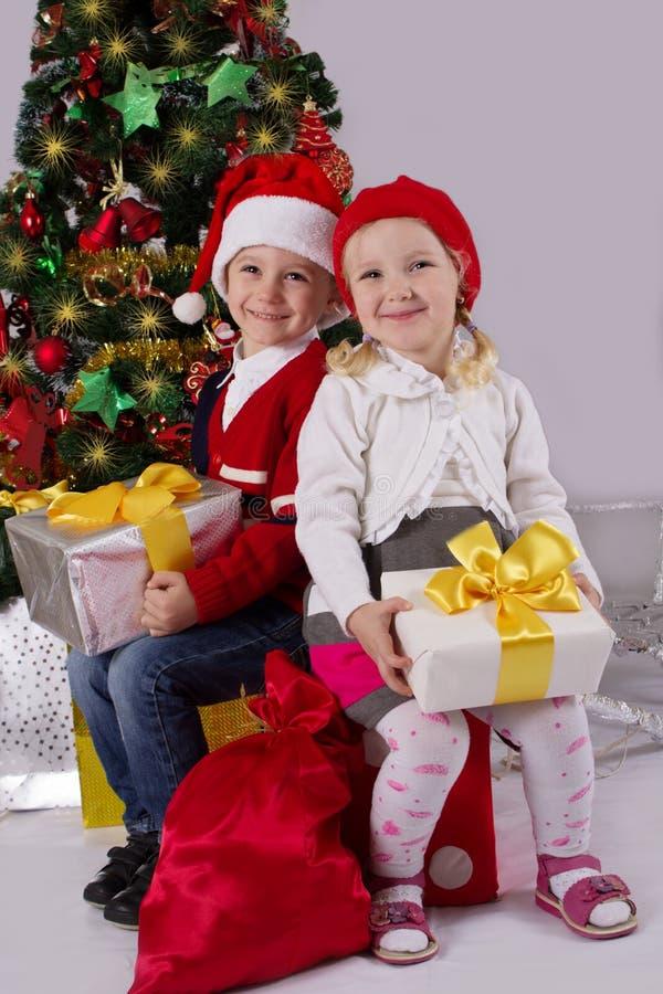 坐与礼物的小女孩和男孩在圣诞树下 库存图片