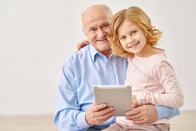 坐与祖父母和桌的孙女 免版税图库摄影