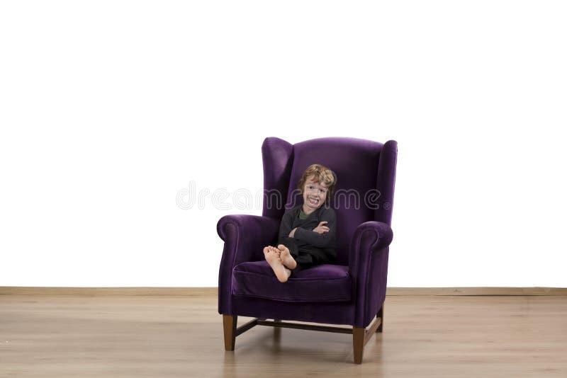 坐与胳膊的无价值孩子在扶手椅子横渡了 免版税图库摄影