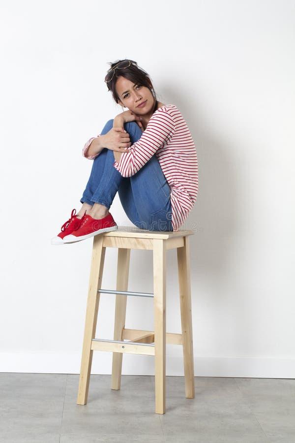 坐与腿的嬉戏的女孩横渡了行动使烦恼 库存照片