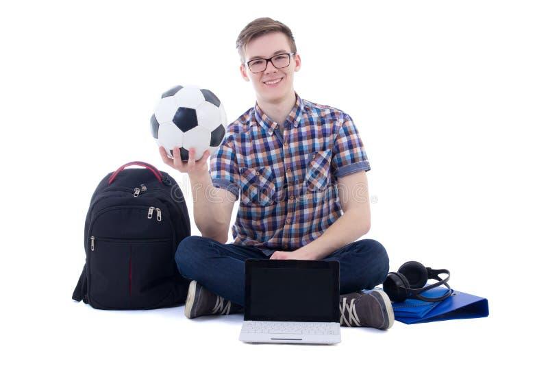 坐与膝上型计算机、背包和足球的愉快的十几岁的男孩 库存照片