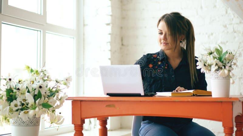 坐与膝上型计算机和写书的年轻美丽的女学生在咖啡馆户内 免版税库存照片