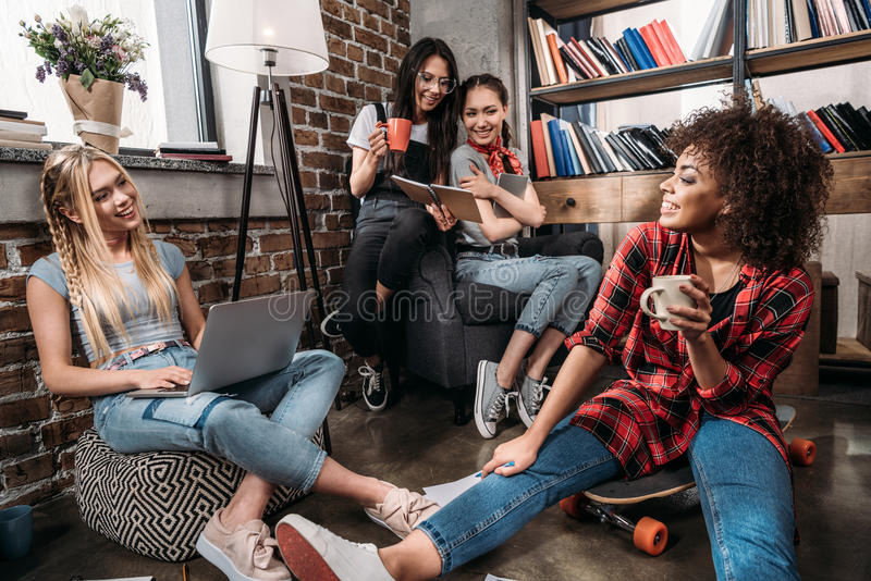 坐与膝上型计算机和咖啡杯一起的微笑的少妇 免版税库存照片