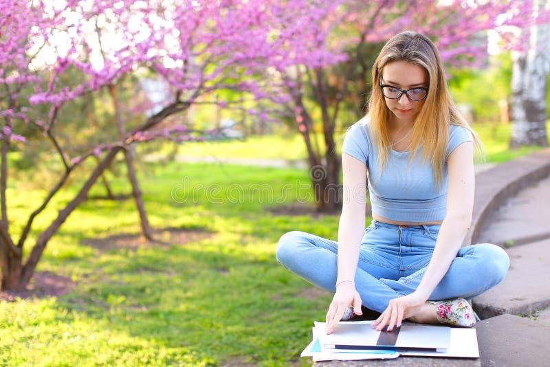 坐与膝上型计算机的女学生在开花的公园 免版税图库摄影