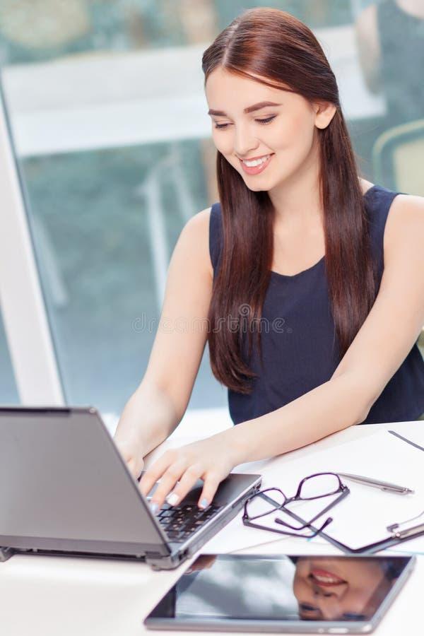 坐与膝上型计算机的欢乐的女孩 免版税库存照片