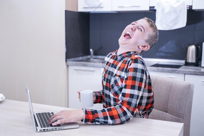 坐与膝上型计算机的积极的生气男孩 有个人计算机的恼怒的情感孩子在家 库存图片