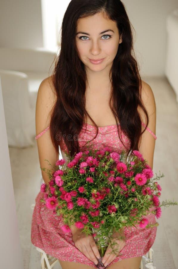 坐与花花束的俏丽的女孩在桃红色花卉dre的 免版税库存图片