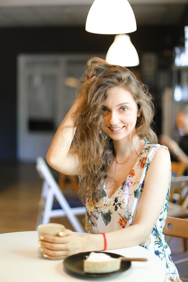 坐与蛋糕和咖啡的年轻白种人妇女在咖啡馆 免版税库存照片