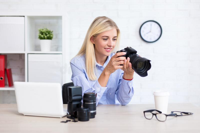 坐与计算机和摄影equipme的妇女摄影师 免版税图库摄影