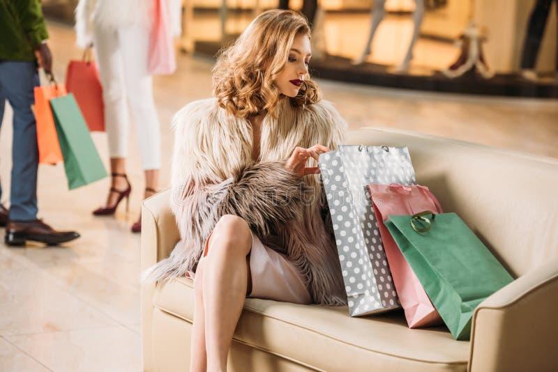 坐与购物袋的皮大衣的时髦的少妇 库存照片