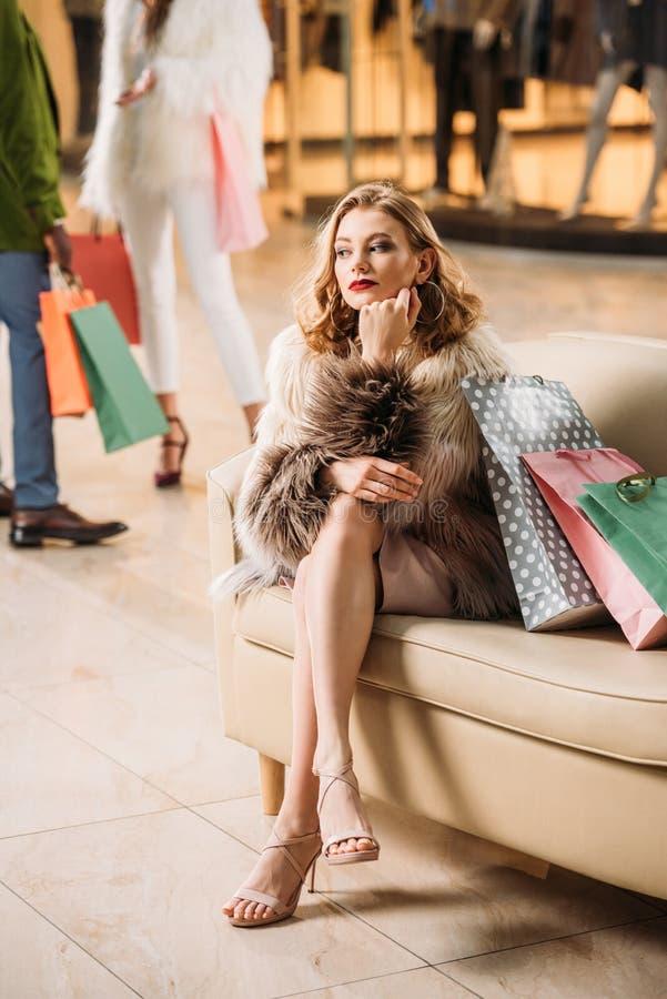 坐与购物袋的皮大衣的沉思少妇 免版税库存照片