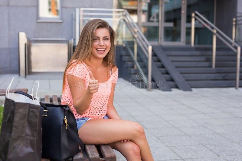 坐与赞许的年轻俏丽的女孩 都市的背景 图库摄影