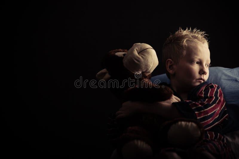 坐与长毛绒玩具的严肃的小男孩 图库摄影