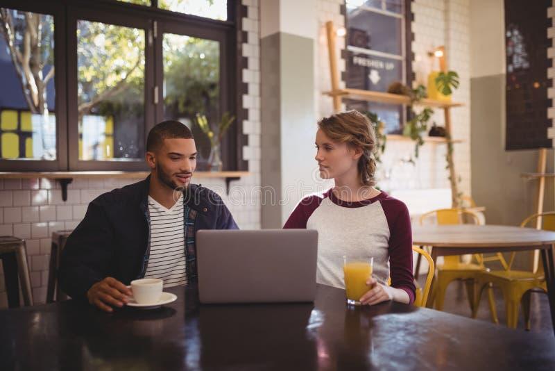 坐与饮料和膝上型计算机的年轻朋友在咖啡店 免版税库存照片