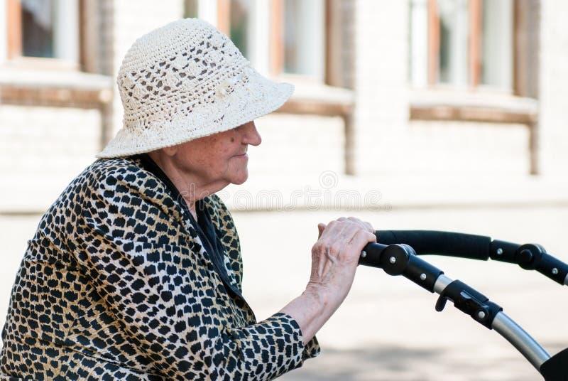 坐与婴儿车的帽子的年长妇女 库存图片