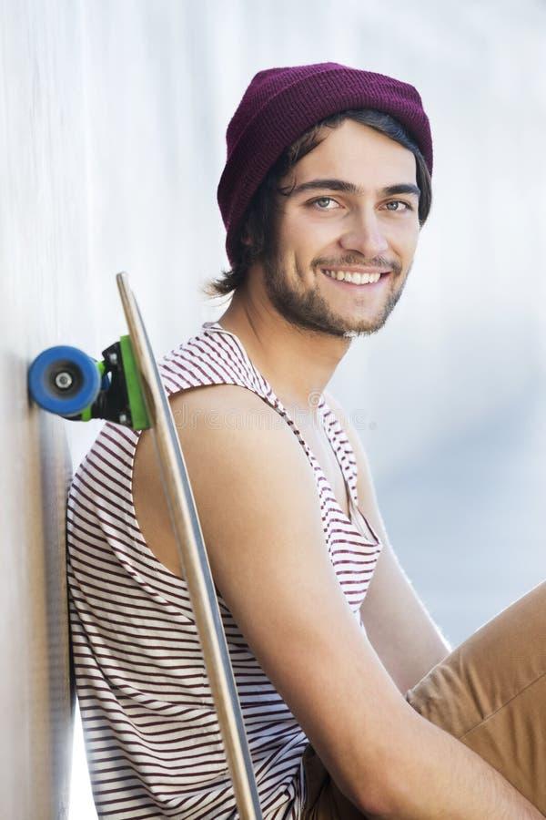坐与滑板的愉快的人 免版税库存照片